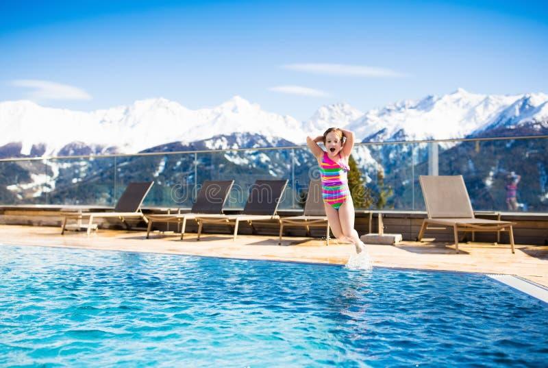 Barn i utomhus- simbassäng av den alpina semesterorten fotografering för bildbyråer