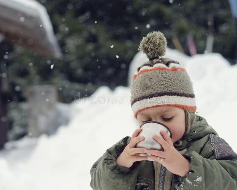 Barn i vinter som dricker varmt te royaltyfria bilder