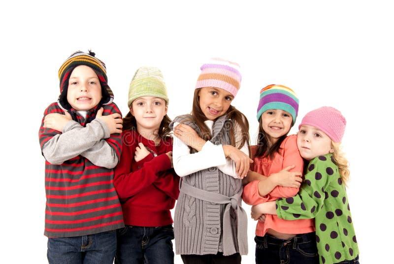 Barn i vinterhattar som huttrar förkylning arkivbilder