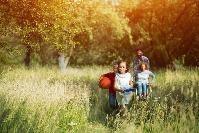Barn körde och skrattet, medan deras moder på rullstolen och fadern jagar dem royaltyfria foton