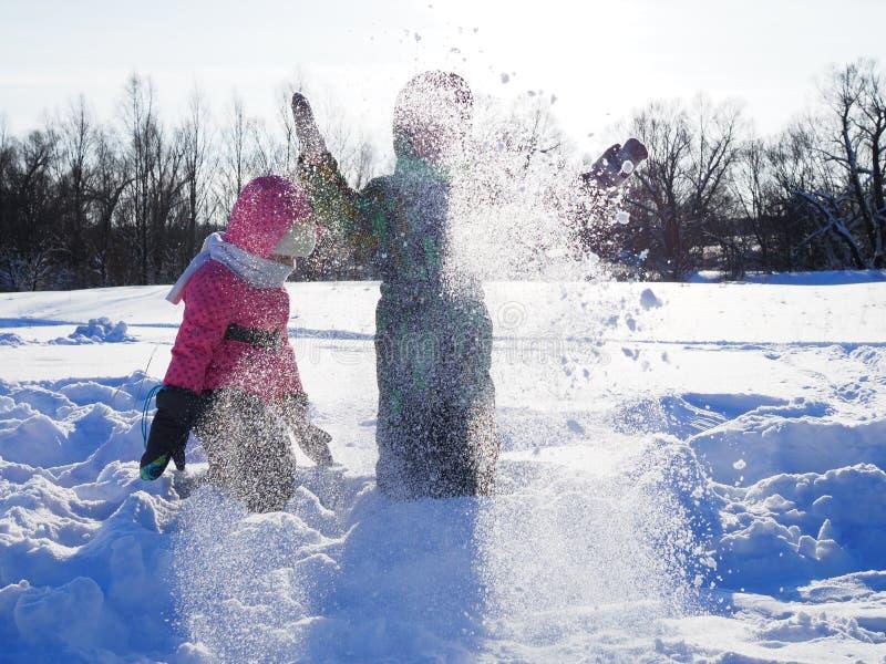 Barn kastar glatt upp fluffig ny snö på en solig vinterdag royaltyfri fotografi