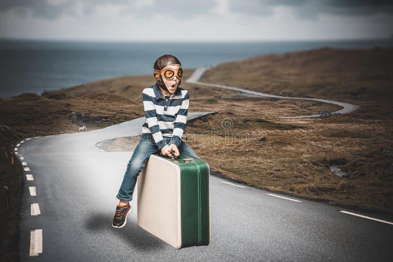 Barn klädd som en stol på en resväska royaltyfria bilder