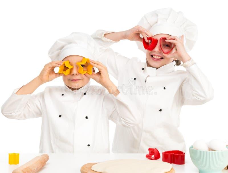 Barn-kockar som spelar former för doughtklipp arkivbild