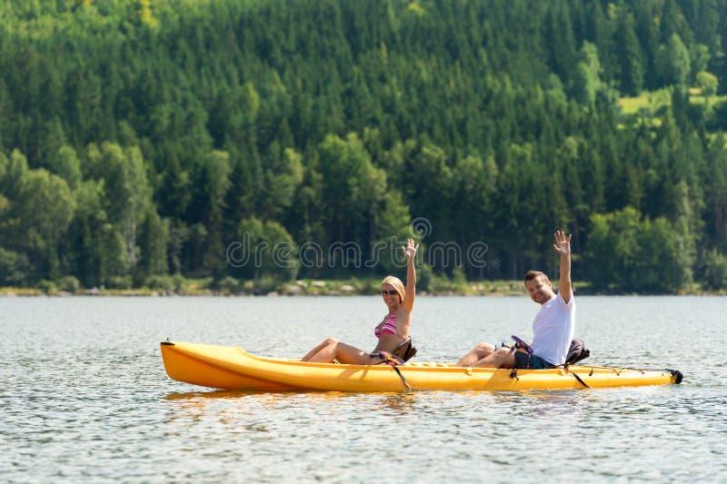 Man och kvinna som kayaking på dammsemester arkivbilder