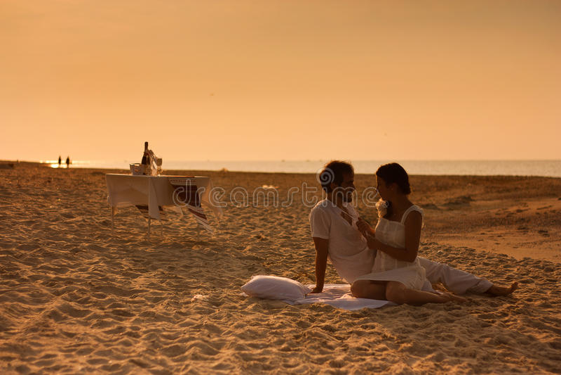 barn kopplar ihop förälskat sammanträde på stranden royaltyfri foto