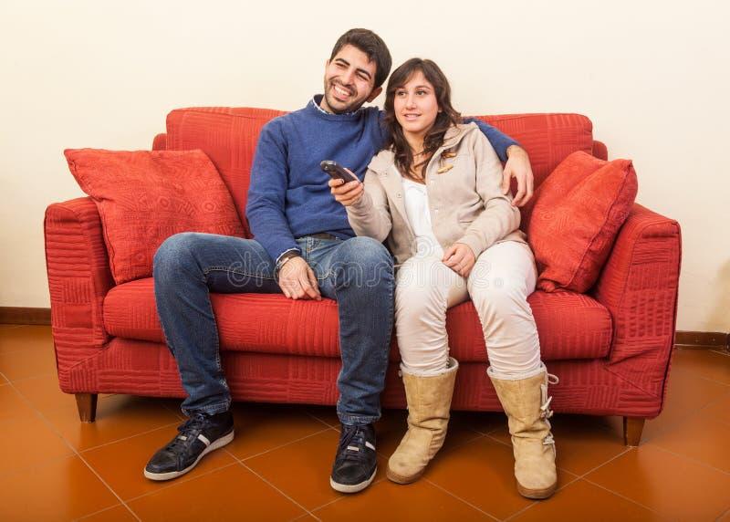 Barn kopplar ihop på sofaen arkivfoton