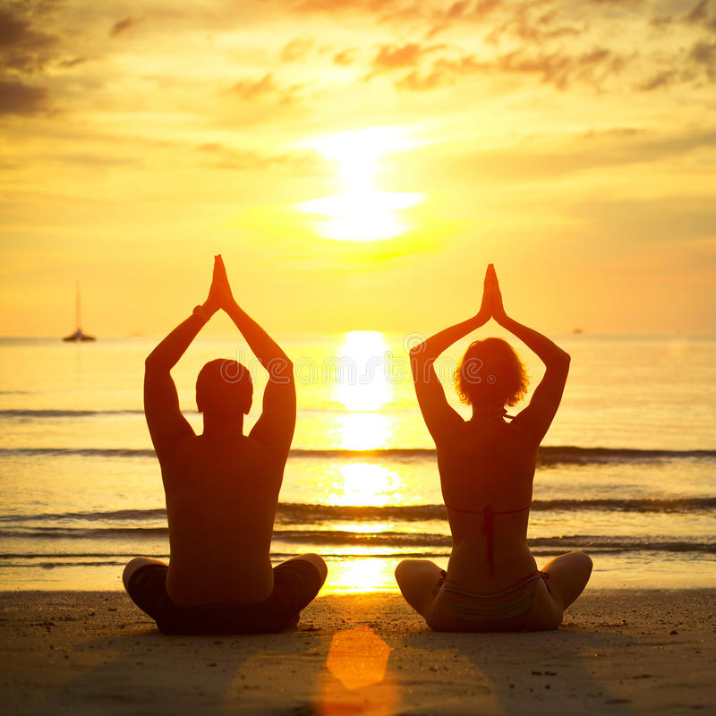 Barn kopplar ihop praktisera yoga på stranden royaltyfri bild