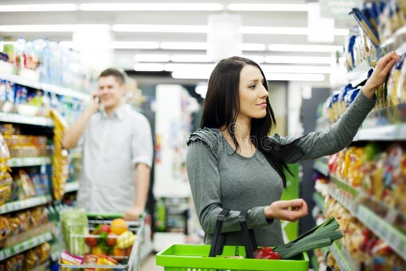 Barn kopplar ihop shopping på supermarketen arkivfoto