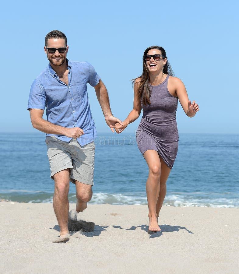Barn kopplar ihop spring på strand royaltyfria foton