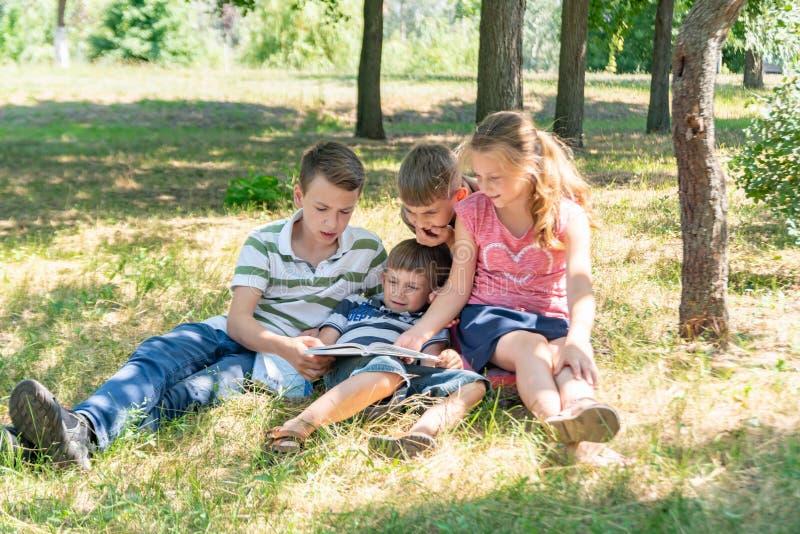Barn lär i natur, fyra barn läste en bok i parkerar i den öppna luften Elever förbereder sig för skola arkivbild