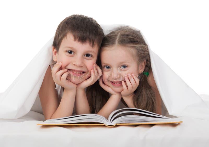 Barn läste en bok i säng royaltyfri bild