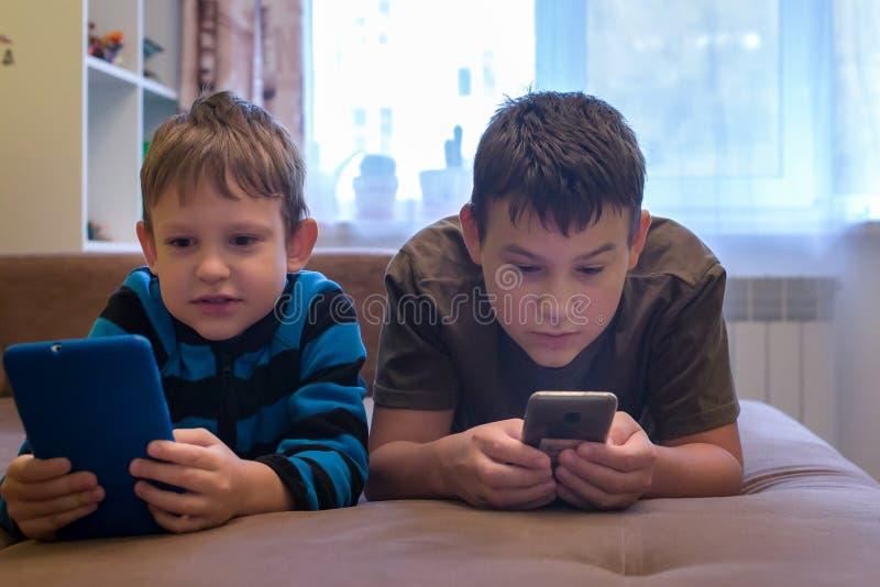 Barn ligger på soffan och spelar i smartphones royaltyfria foton