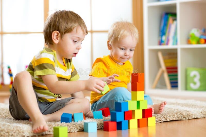Barn litet barn och förskolebarnpojkar som spelar leksaken, blockerar hemma eller barnkammaren royaltyfri bild