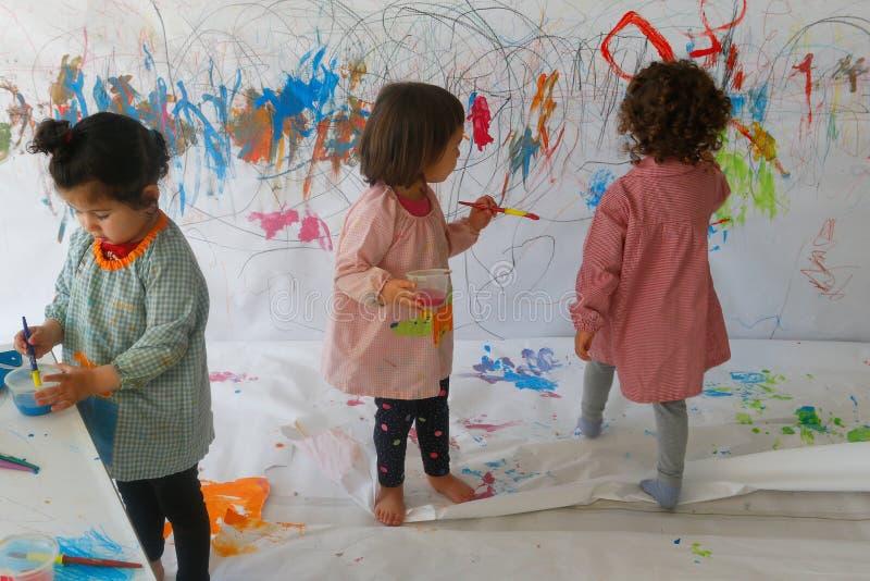 Barn målar genom att använda vattenfärger inom deras klassrum royaltyfri foto