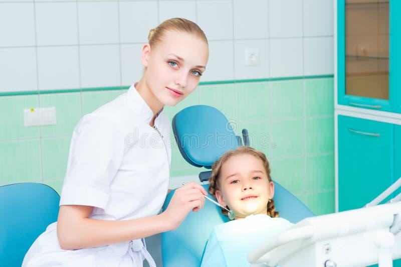 Barn manipulerar kvinnan och flickan i tandläkarekontor arkivbild
