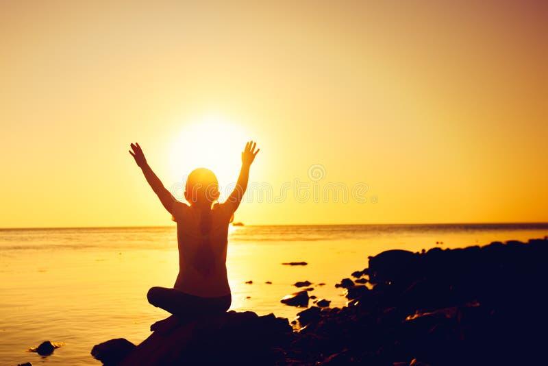 Barn med öppna armar på solnedgången på stranden Solnedgångskott, bakre sikt sun för hav för bakgrundsfiordsstråle arkivbilder