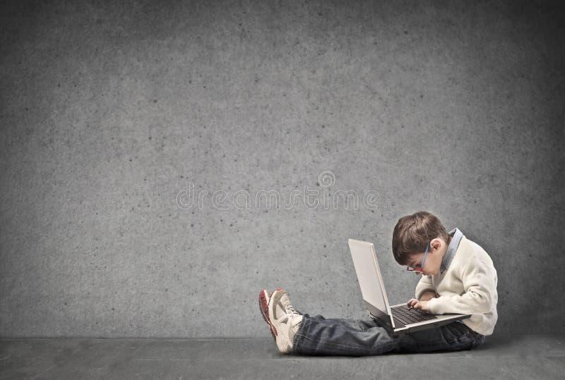Barn med bärbar dator royaltyfri foto