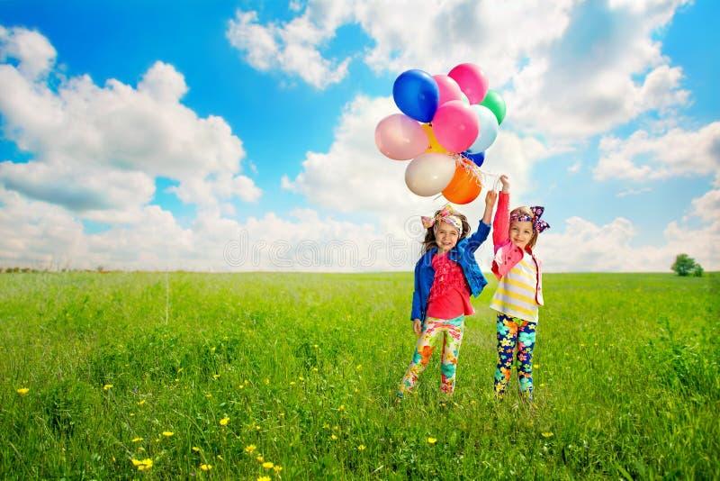 Barn med ballonger som går på vårfält royaltyfri foto