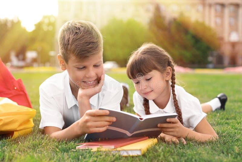 Barn med brevpapper som gör skolauppgift på gräs royaltyfria foton