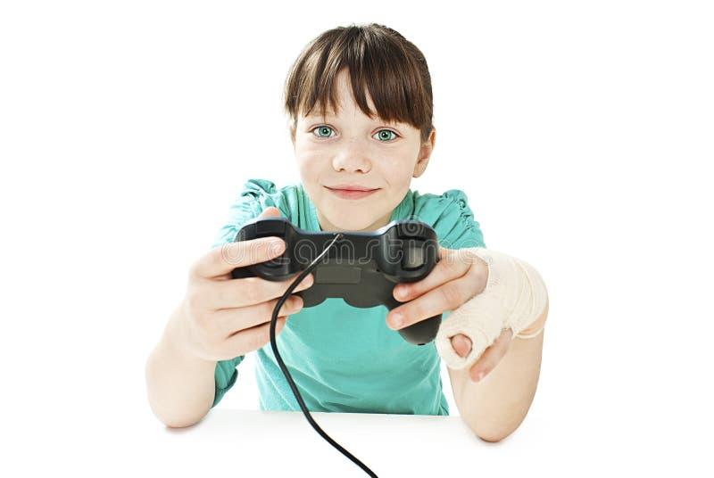 Barn med den brutna armen genom att använda videospelkontrollanten royaltyfria foton