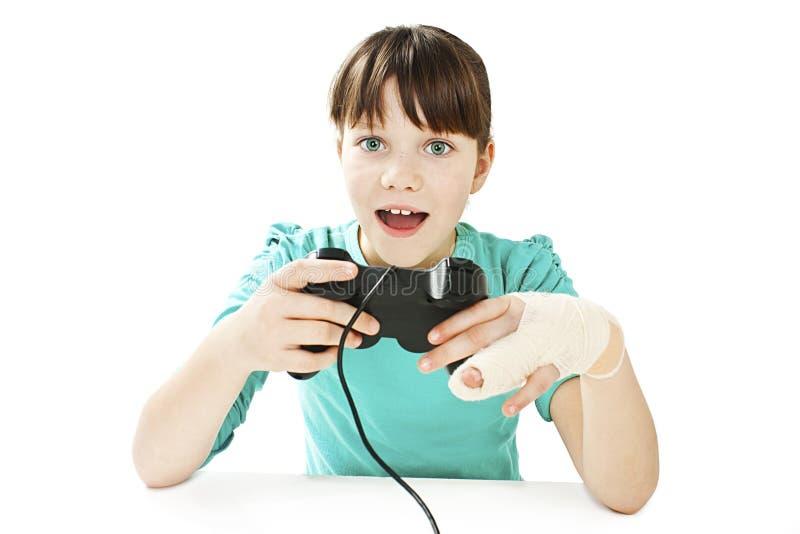 Barn med den brutna armen genom att använda videospelkontrollanten fotografering för bildbyråer