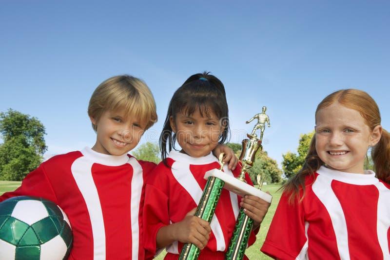 Barn med den fotbollbollen och trofén arkivbild