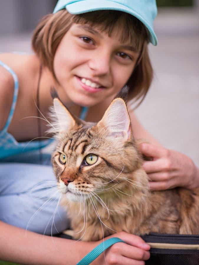 Barn med den Maine Coon kattungen fotografering för bildbyråer