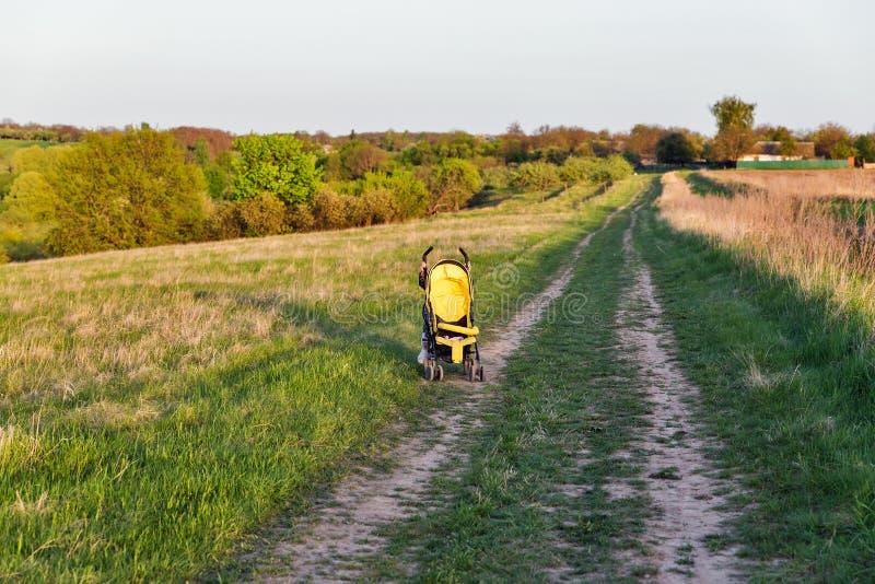 Barn med en barnvagn i det lantliga landskapet för afton royaltyfria foton
