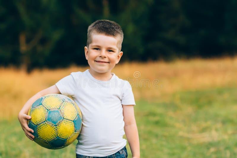Barn med en fotbollboll under hans arm på husträdgården med gräsbakgrund som ler Ungesport och fotbollvärldscup arkivfoton