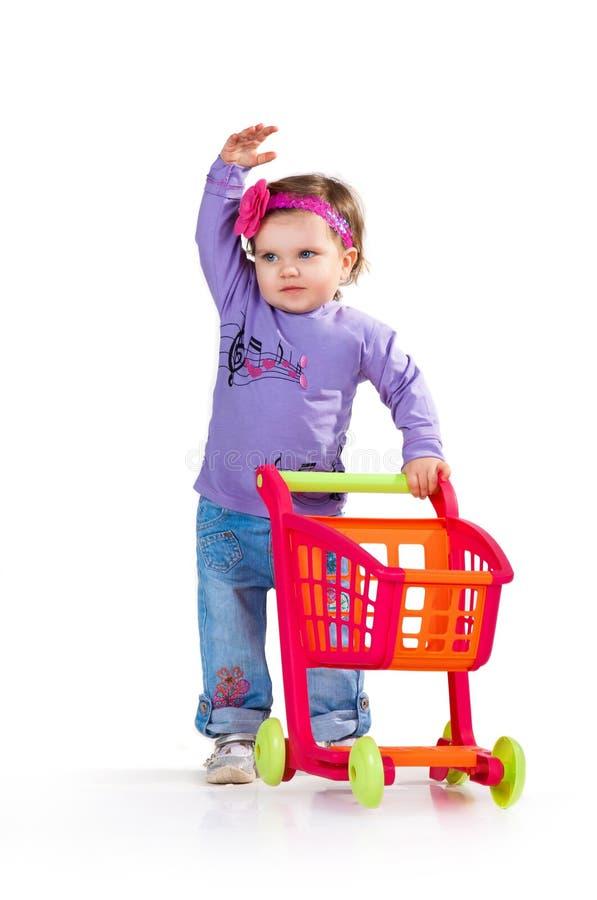 Barn med en leksakshoppingspårvagn arkivfoton