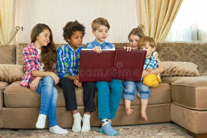 Barn med en stor bok royaltyfria foton