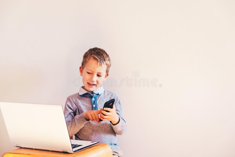 Barn med ett mycket uttrycksfullt ansikte framför en bärbar dator samtidigt som du använder en smart telefon för att göra affärer arkivbild