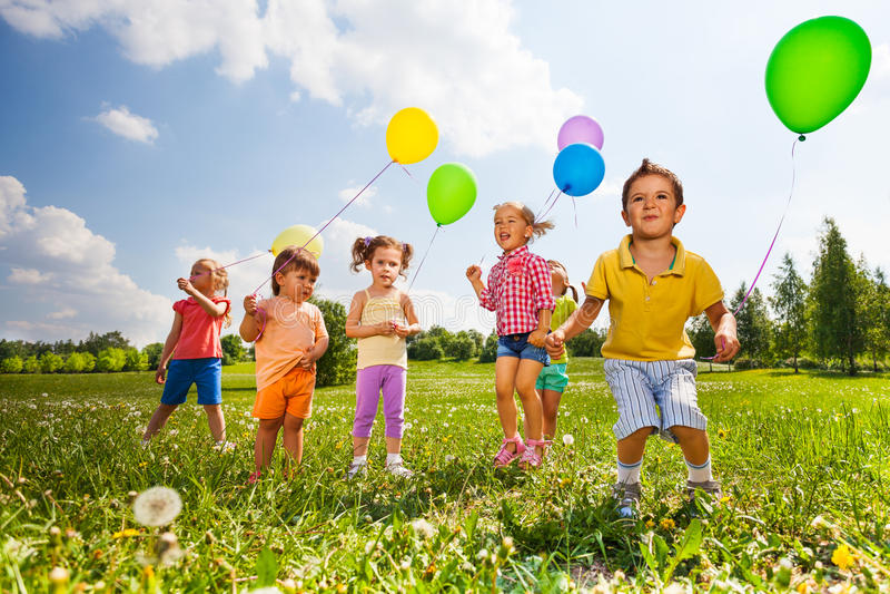 Barn med färgrika ballonger som kör i fält royaltyfri foto