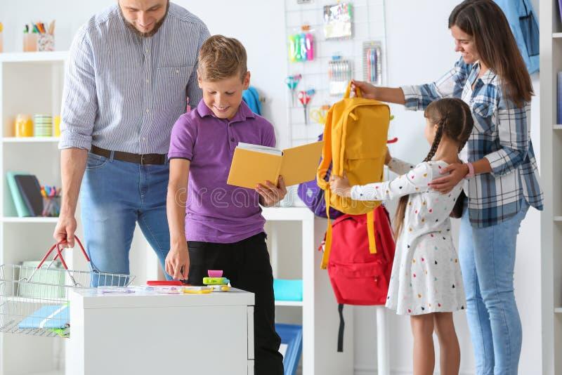 Barn med föräldrar som väljer skolabrevpapper arkivfoton