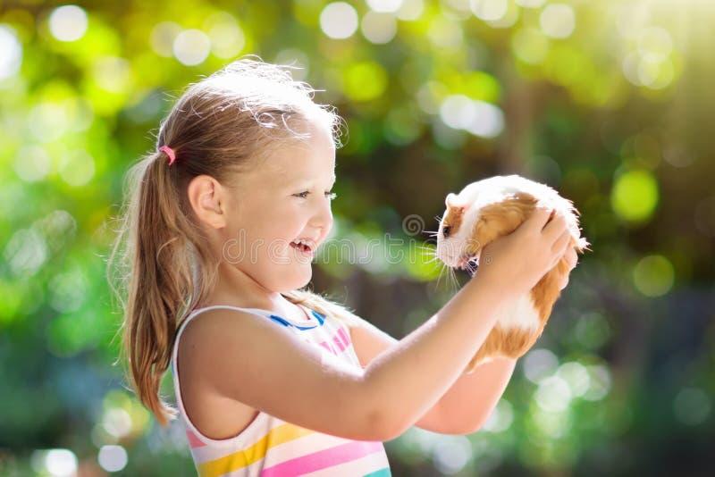Barn med försökskaninen Cavydjur Ungar och husdjur arkivfoton