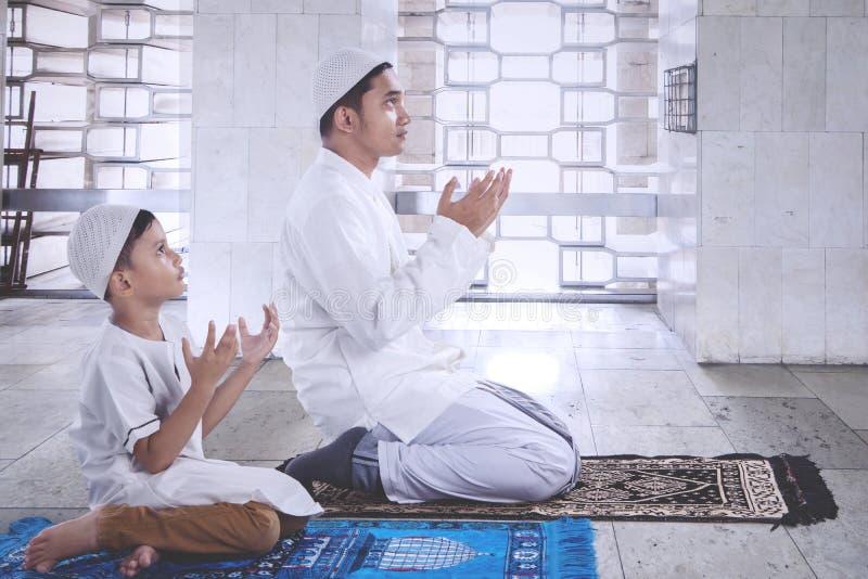 Barn med fadern som tillsammans ber i moskén royaltyfri fotografi