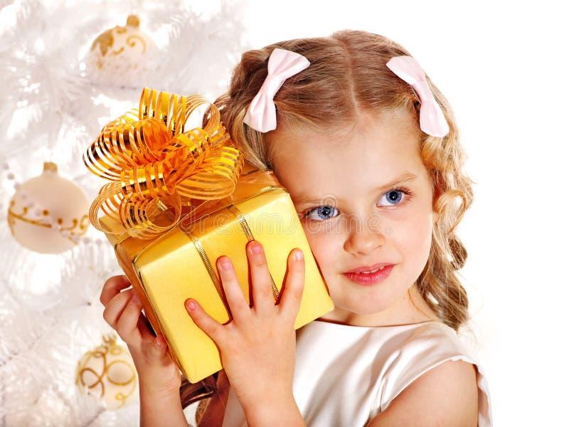 Barn med gåvaasken nära den vita julgranen. arkivfoton