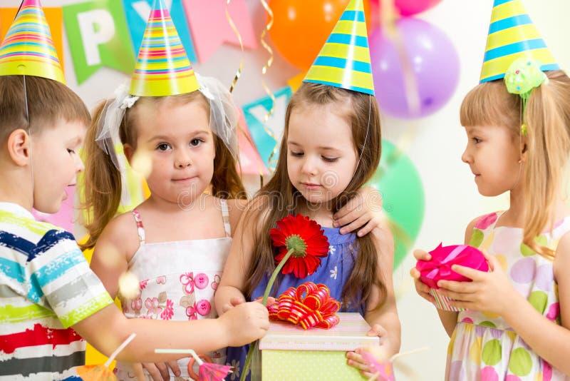 Barn med gåvor på födelsedagpartiet arkivbild