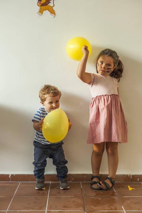 Barn med gula ballonger som har gyckel i ungar, festar royaltyfria bilder