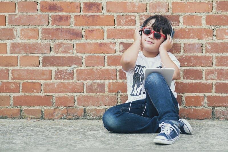 Barn med hörlurar förbindelse med den digitala minnestavlan arkivbilder