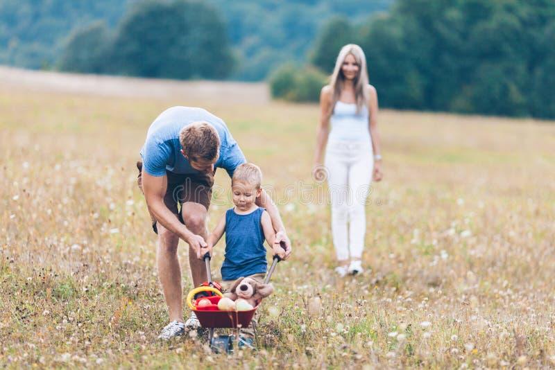 Barn med hans föräldrar som utomhus skjuter en whellbarrow royaltyfria bilder