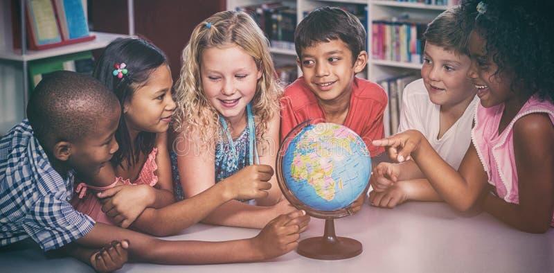 Barn med jordklotet på tabellen arkivfoton