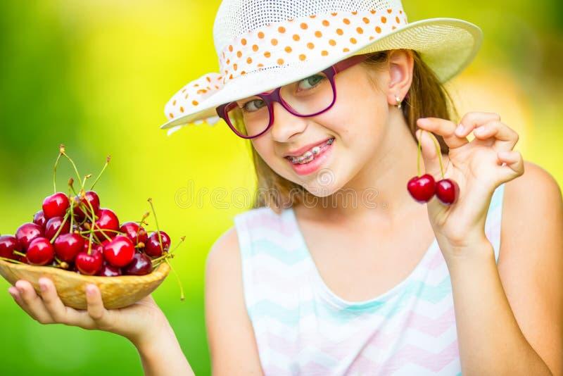Barn med körsbär Liten flicka med nya körsbär Bärande tandhänglsen och exponeringsglas för ung gullig caucasian blond flicka arkivfoto