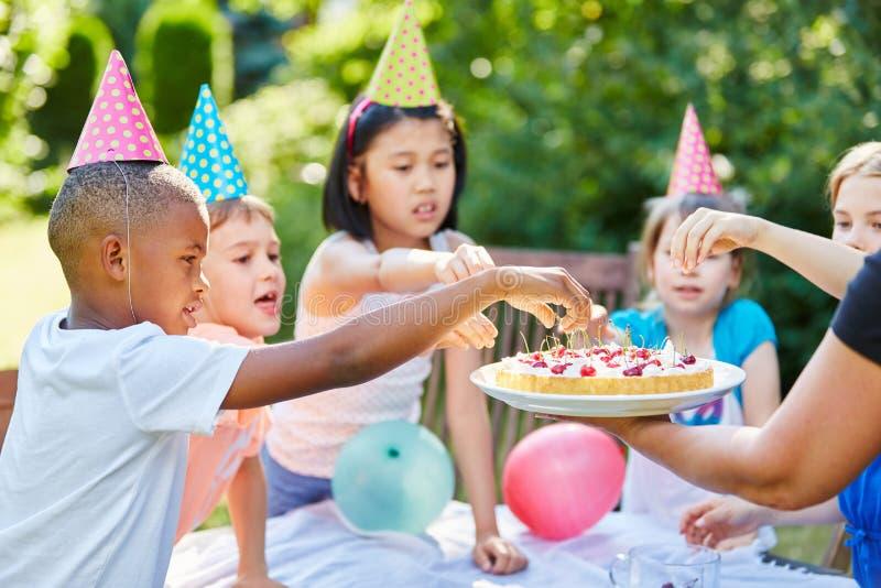 Barn med kakan på födelsedagen arkivbild