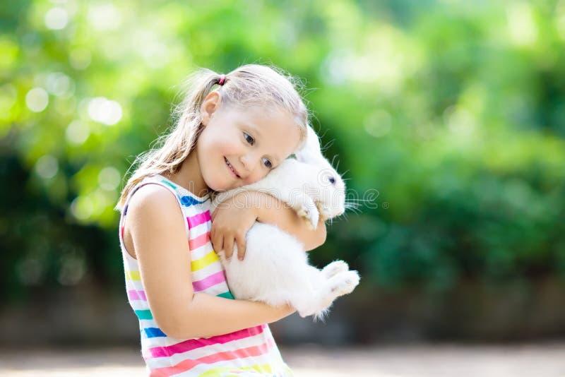 Barn med kanin kanin easter Ungar och husdjur arkivfoton