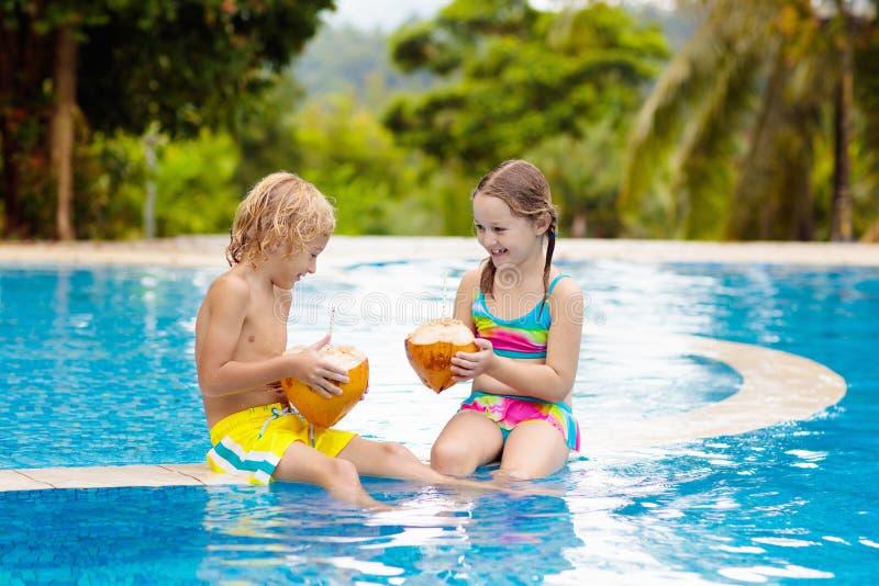 Barn med kokosnötdrinken Ungar i simbass?ng arkivfoto