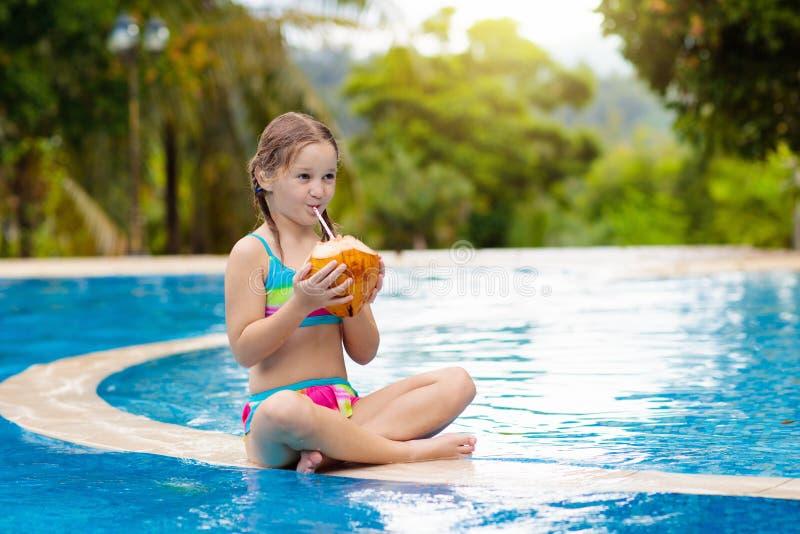 Barn med kokosnötdrinken Ungar i simbass?ng arkivbild