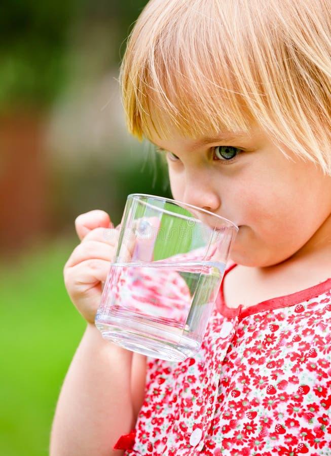 Barn med koppen av vatten arkivbilder