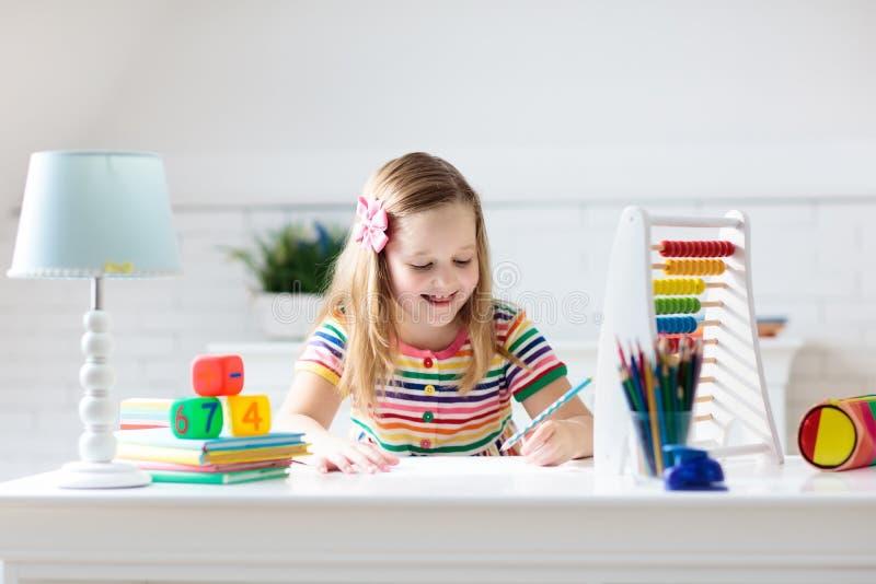 Barn med kulrammet som gör läxa efter skola arkivbild
