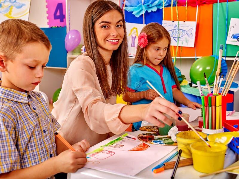 Barn med lärarekvinnamålning på papper in royaltyfri fotografi